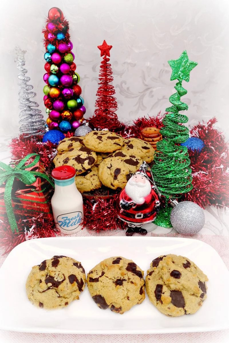 Homemade soft and chewy Paleo chocolate chip cookies on a white plate with a plate full of chocolate chip cookies in the background with Christmas decorations