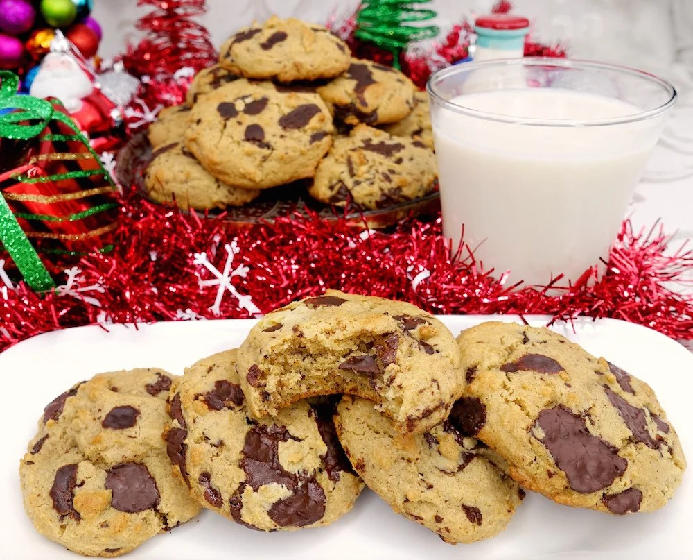 A white rectangular plate with homemade soft and chewy Paleo chocolate chip cookies, with a bite taken out of one. A glass of milk and additional cookies and Christmas decor in the background