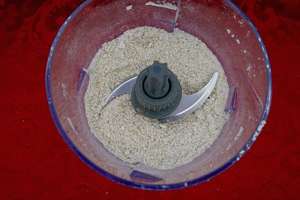 Homemade gluten-free oat flour in a small blender over a red background