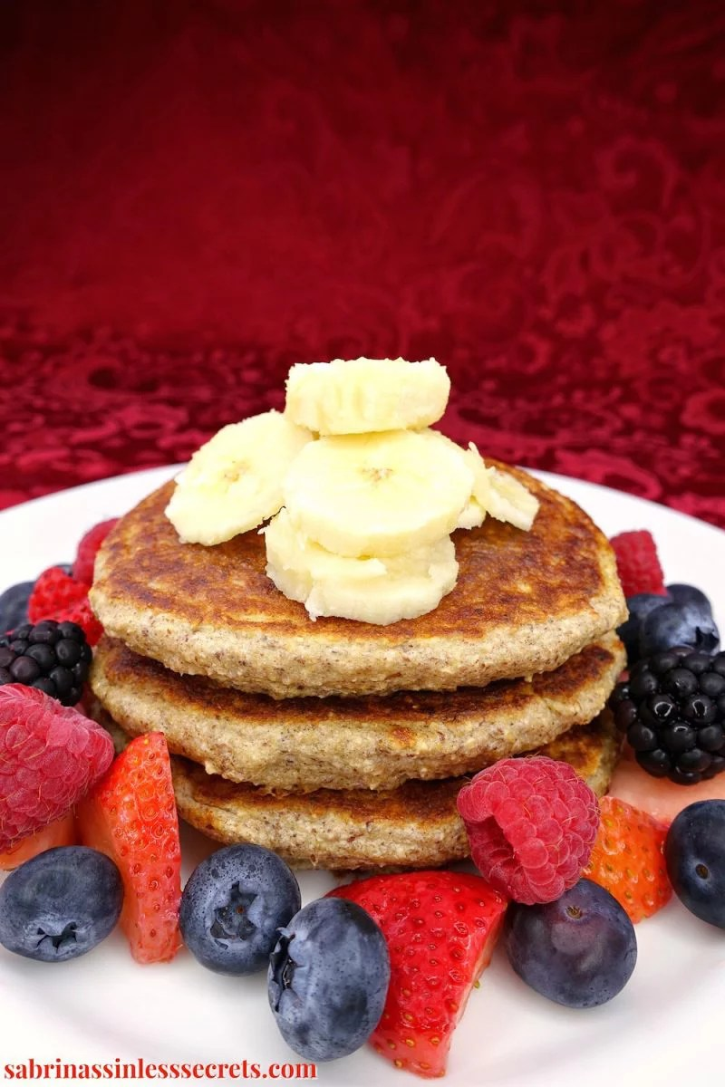 A stack of healthy homemade gluten-free greek yogurt oat pancakes on a white plate, topped with banana slices, with strawberries, blueberries, raspberries, and blackberries surrounding them