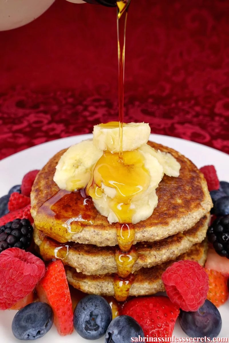 Maple syrup being poured over a stack of healthy homemade gluten-free greek yogurt oat pancakes that are on a white plate, topped with banana slices and surrounded by strawberries, blueberries, raspberries, and blackberries