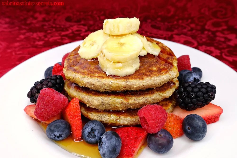 A stack of healthy homemade gluten-free greek yogurt oat pancakes on a white plate, topped with banana slices and drizzled with maple syrup with strawberries, blueberries, raspberries, and blackberries surrounding them