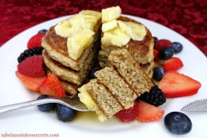 A stack of homemade gluten-free greek yogurt oat pancakes on a white plate, topped with banana slices, sliced strawberries, blueberries, raspberries, blackberries, and maple syrup with a bundle of pancakes on a fork
