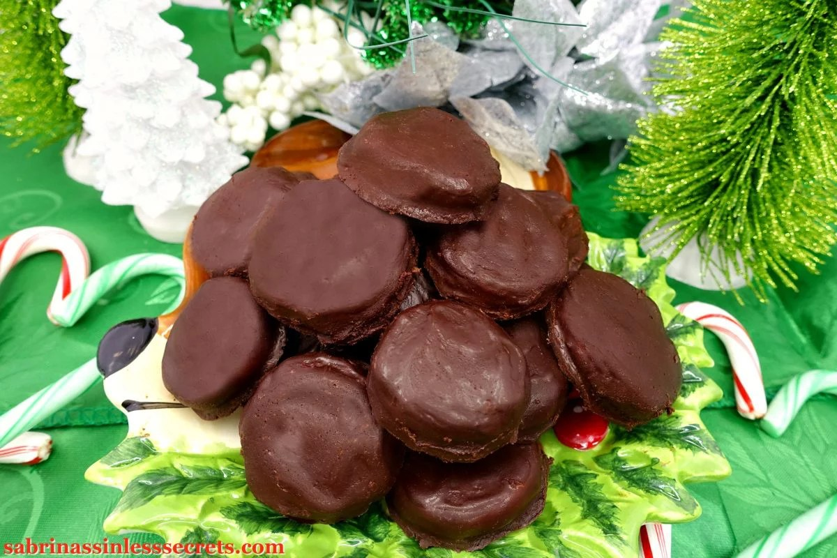a mountain of Paleo Peppermint Patties on a reindeer plate on a green tablecloth with candy canes, Christmas trees, and festive flowers