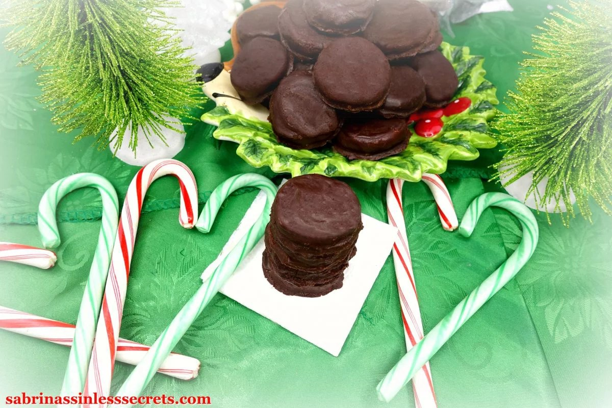 A stack of Paleo Peppermint Patties on a white napkin atop a green tablecloth with heart-shaped candy canes around it and a plate of Paleo Peppermint Patties in the background