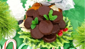 A plate of Paleo Peppermint Patties with fresh mint leaves on top