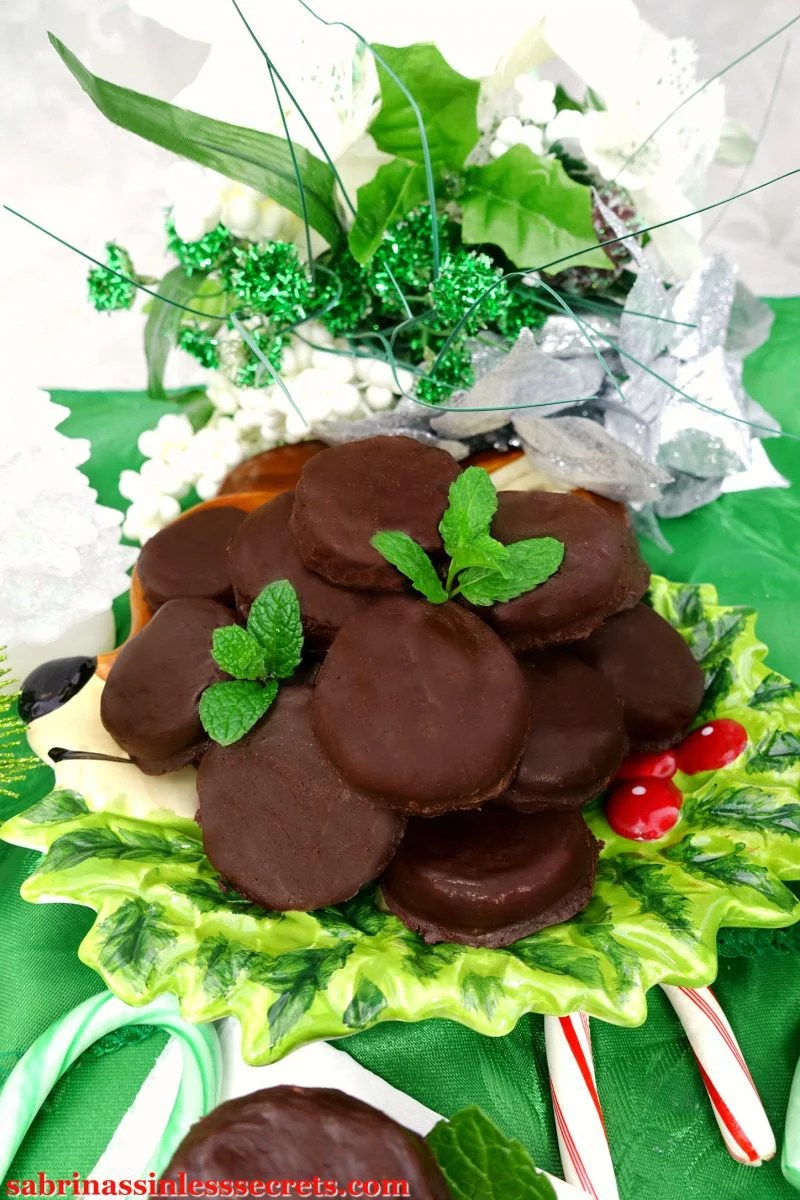 A mountain of Paleo Peppermint Patties with fresh mint leaves on top, resting on a festive reindeer plate on top of a green tablecloth