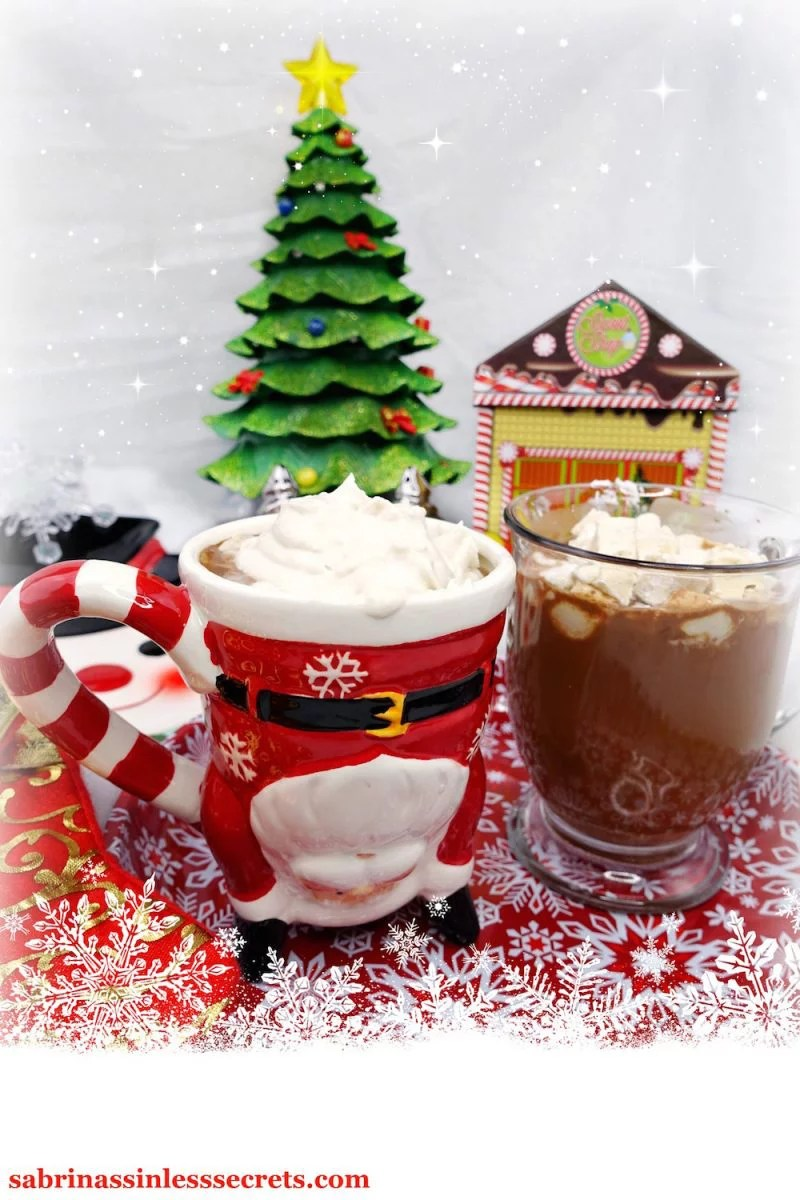 A santa mug with Paleo hot chocolate and Paleo whipped cream on top, alongside a clear mug full of Paleo hot chocolate with homemade Paleo marshmallows on top—sitting on a red and white snowflake plate and a Christmas tree and other decorations in back