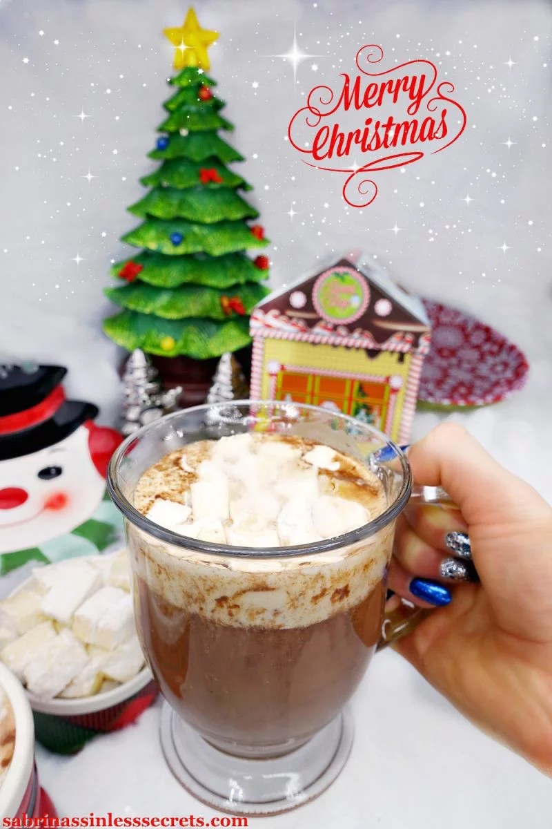 A hand holding Paleo hot chocolate in a clear mug with homemade Paleo marshmallows on top and with Christmas decorations in the background