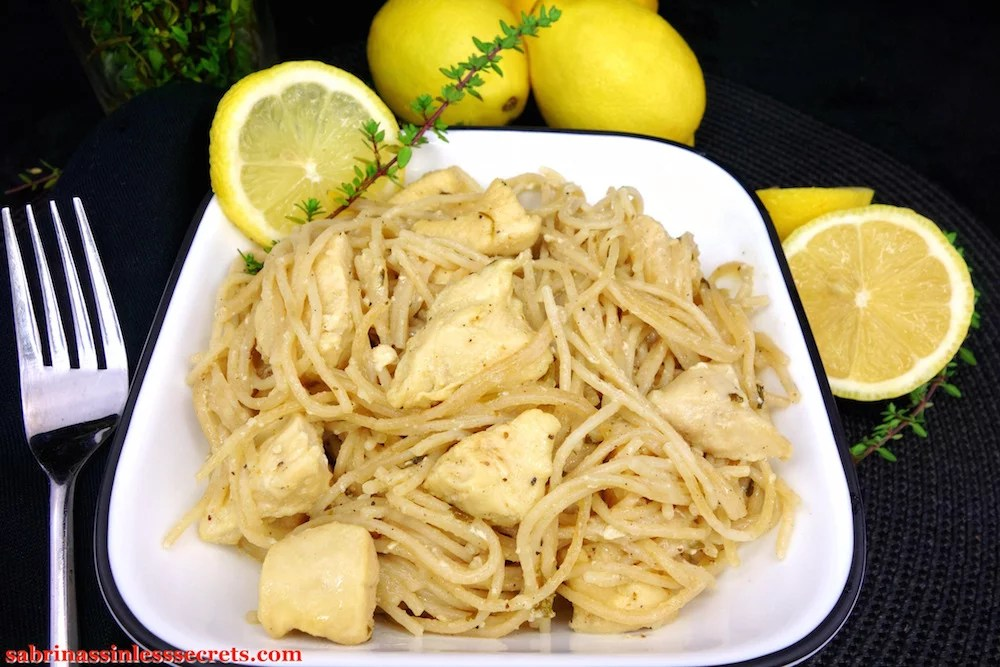 Lemon Thyme Honey Chicken with Angel Hair Pasta in a square white bowl, garnished with a lemon slice and a lemon thyme with lemons and lemon thyme in the black background
