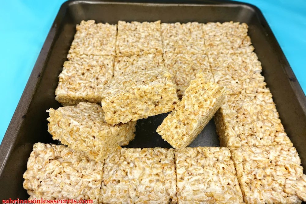 Freshly cut healthy brown rice crispy treats in a 9x9-inch pan with three healthy brown rice crispy treats angled up and in different directions