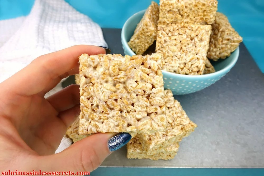 A hand holding a Healthy Brown Rice Crispy Treat made with Paleo marshmallows with more Healthy Brown Rice Crispy Treats in a blue bowl with white dots in the background