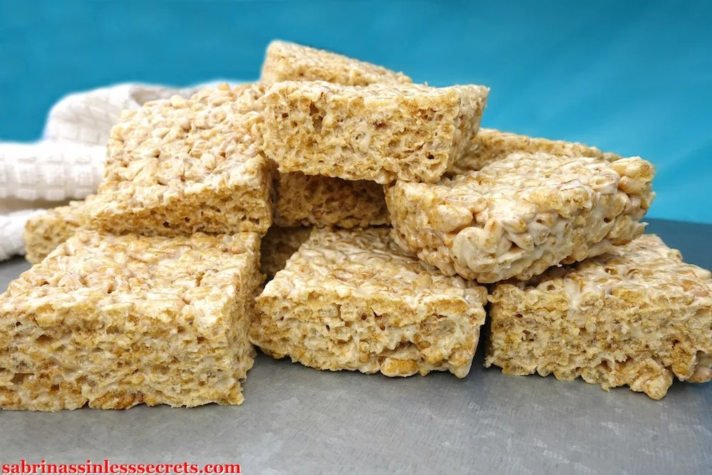 A stack of Healthy Brown Rice Crispy Treats made with Paleo marshmallows on a silver platform and with a blue background