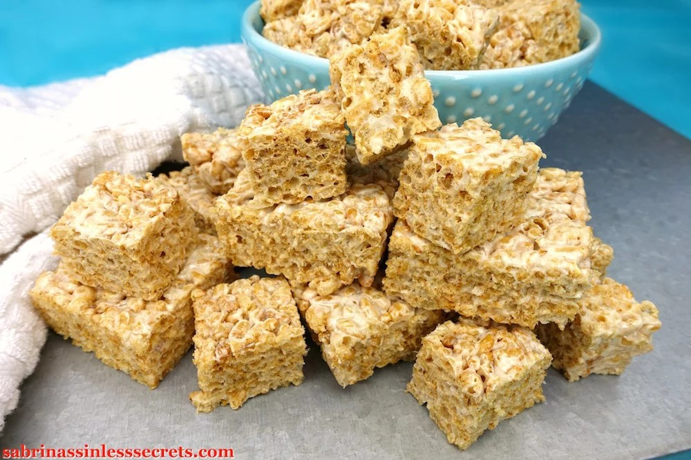 Healthy Brown Rice Crispy Treats (or Bites) stacked on top of each other on a silver platform with a blue bowl with white dots full of more healthy brown rice crispy bites in the background