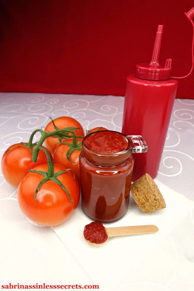 A glass jar full of homemade Quick & Easy Paleo Ketchup, surrounded by a red, rubber ketchup bottle, fresh tomatoes on the vine, and a wooden spoon full of ketchup