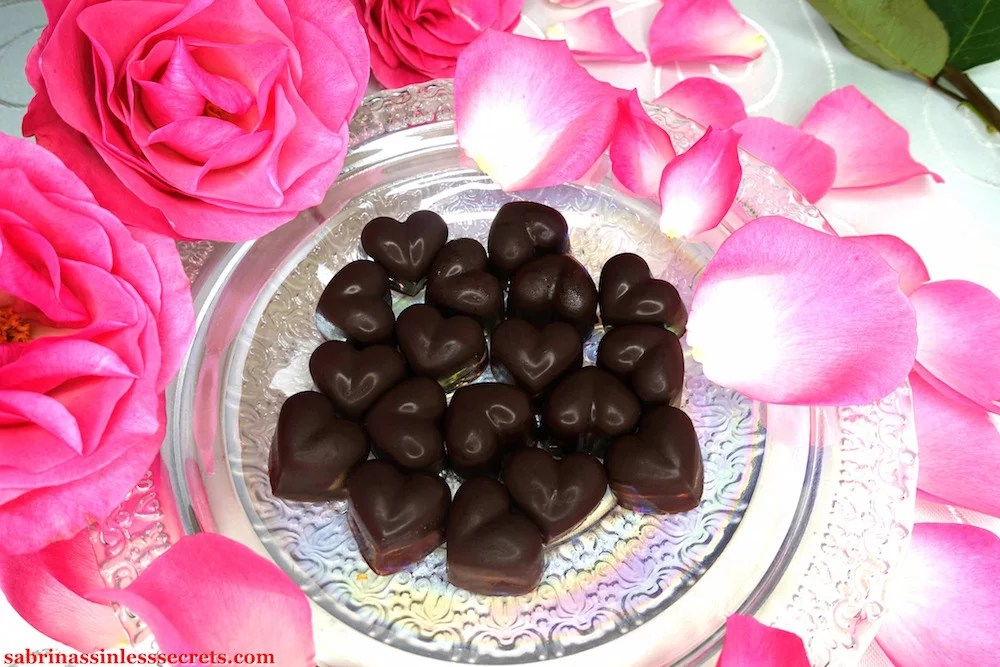 Homemade heart-shaped dark chocolate Paleo Raspberry Cream Truffles on a pearlescent dish encircled with fresh pink roses and rose petals