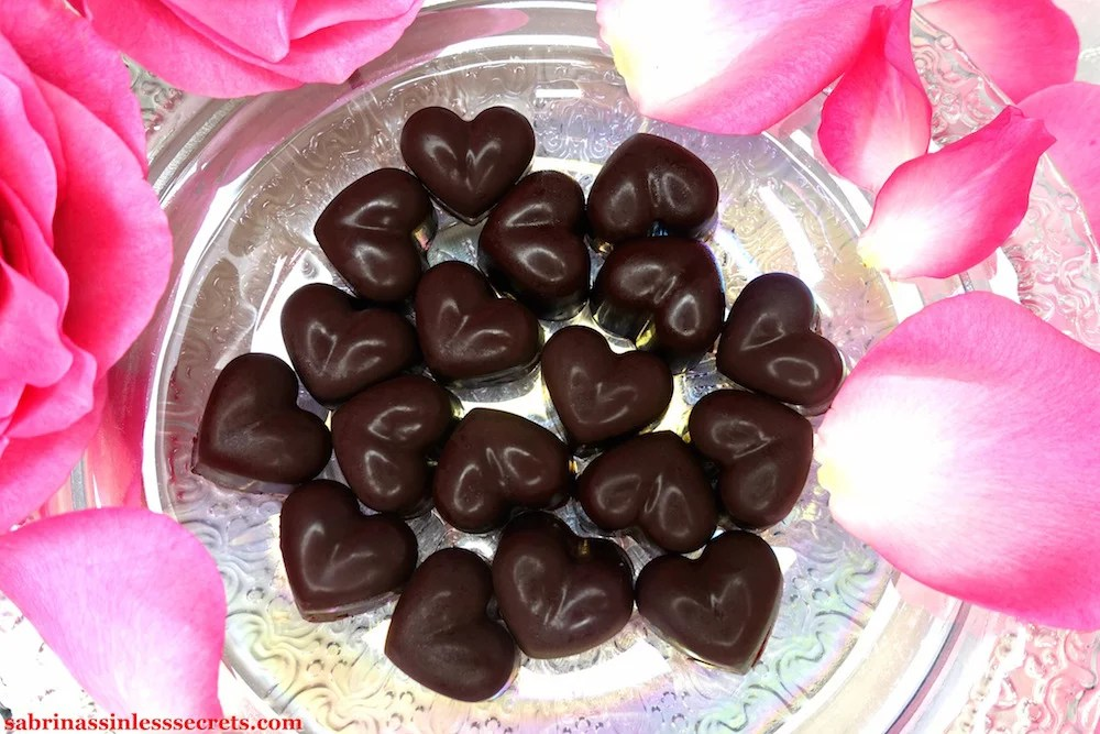 Homemade heart-shaped dark chocolate Paleo Raspberry Cream Truffles on a pearlescent plate with pink roses surrounding them