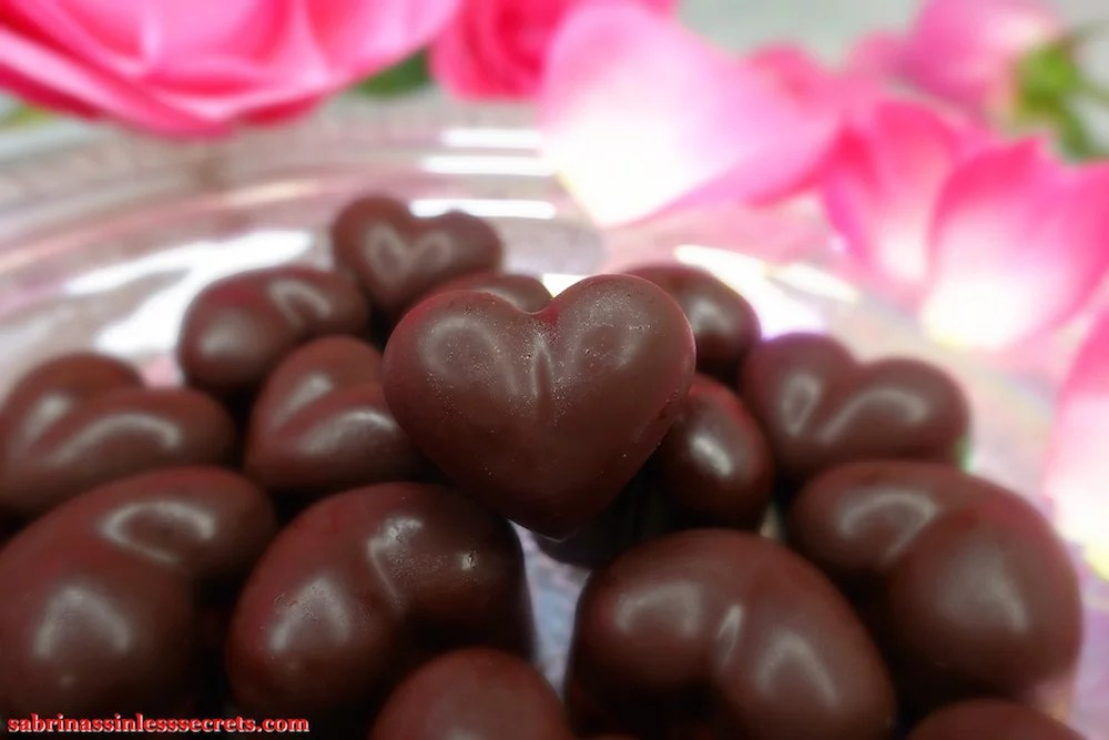 A close up of homemade heart-shaped dark chocolate Paleo Raspberry Cream Truffles with pink roses in the background