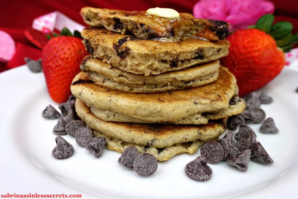 A stack of homemade Paleo Dark Chocolate Chip Pancakes from the side with the top two being heart-shaped on a white plate, surrounded by chocolate chips and fresh strawberries