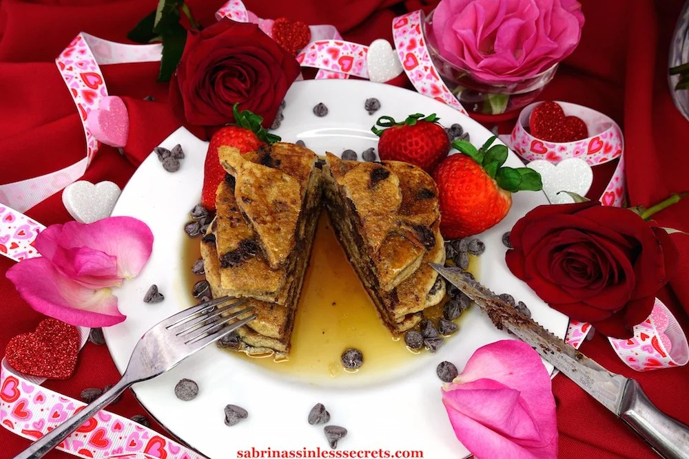 Homemade Paleo Dark Chocolate Chip Pancakes cut down the middle after being poured with maple syrup on a white plate with fresh strawberries, chocolate chips, and red and pink roses