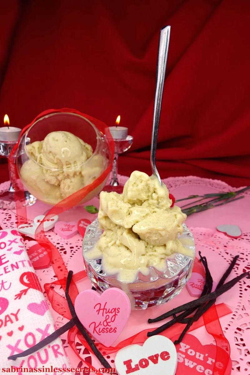 A messy mountain of Creamy Vanilla Bean Paleo Ice Cream in a chilled crystal bowl with a spoon sticking on the top, surrounded by fresh vanilla bean pods, hearts with messages, and more ice cream in a glass stand-up bowl behind, with tea light candles resting atop crystal candles holders by its side