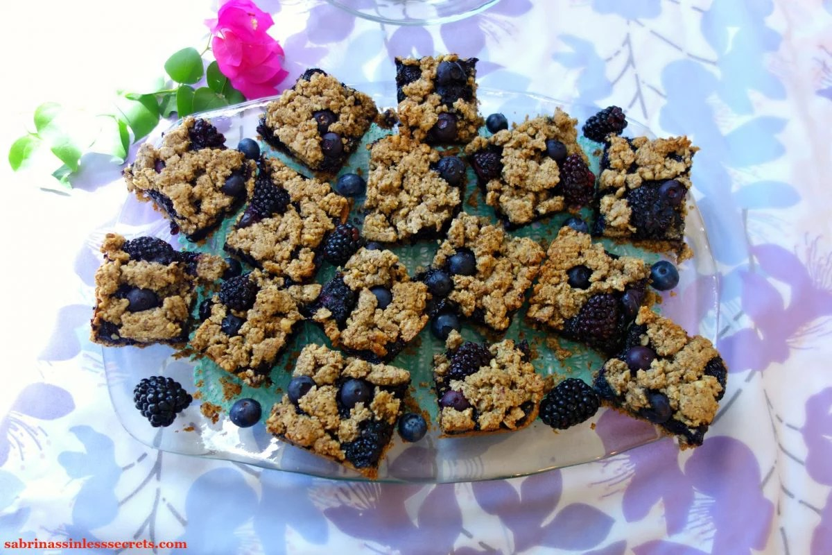 A plate of arranged Black & Blueberry Gluten-Free Crumble Bars, resting on a floral lavender and light blue tablecloth with a fascia flower