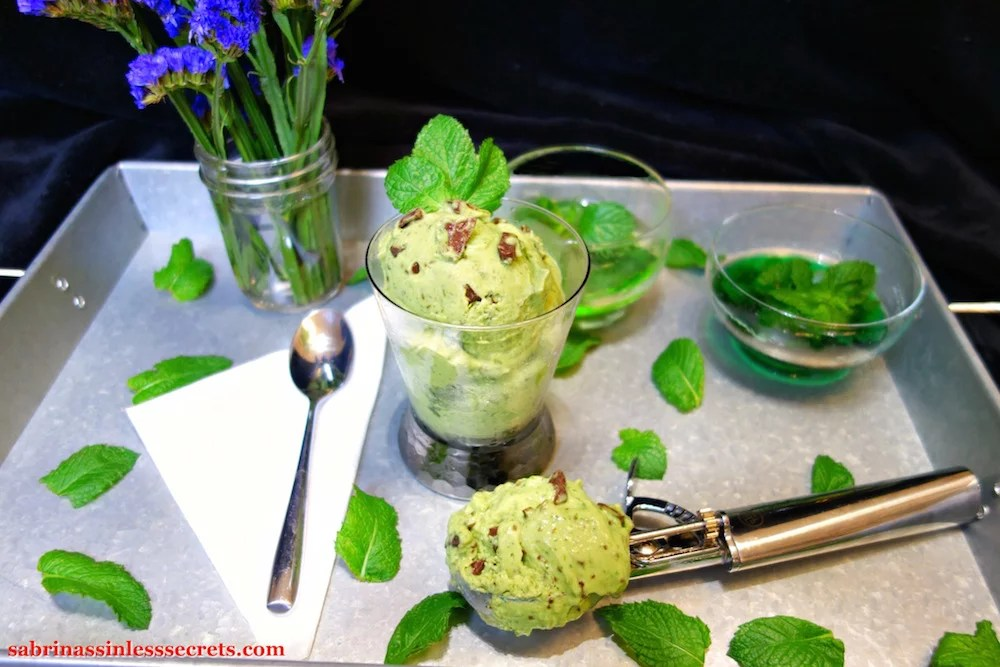 A silver tray holding a chilled glass of homemade Paleo Mint Chocolate Chip Ice Cream, garnished with fresh mint leaves, a stainless steel ice cream scooper full of more ice cream, a white paper napkin with a stainless steel spoon resting atop it, scattered fresh mint leaves, two glass bowls full of green water with floating mint leaves, and a mason jar full of indigo flowers