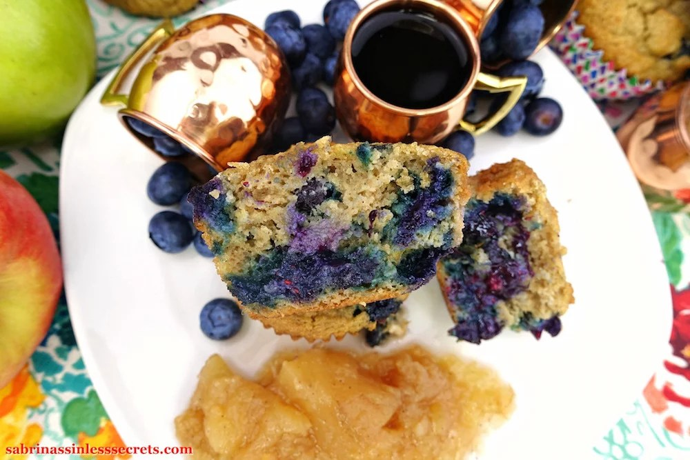 A cut open Apple Blueberry Paleo Muffin facing upward, sitting atop a stack of muffins with the other open half on the white plate they're resting on, joined by a side of homemade chunky Paleo applesauce, two petite copper mugs turned over with fresh blueberries and another with hot black coffee