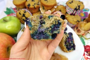 A hand holding a cut open Apple Blueberry Paleo Muffin, showing the beautiful blueberry insides with an assortment of stacked and leaning muffins in the background and a honey crispy and granny smith apple