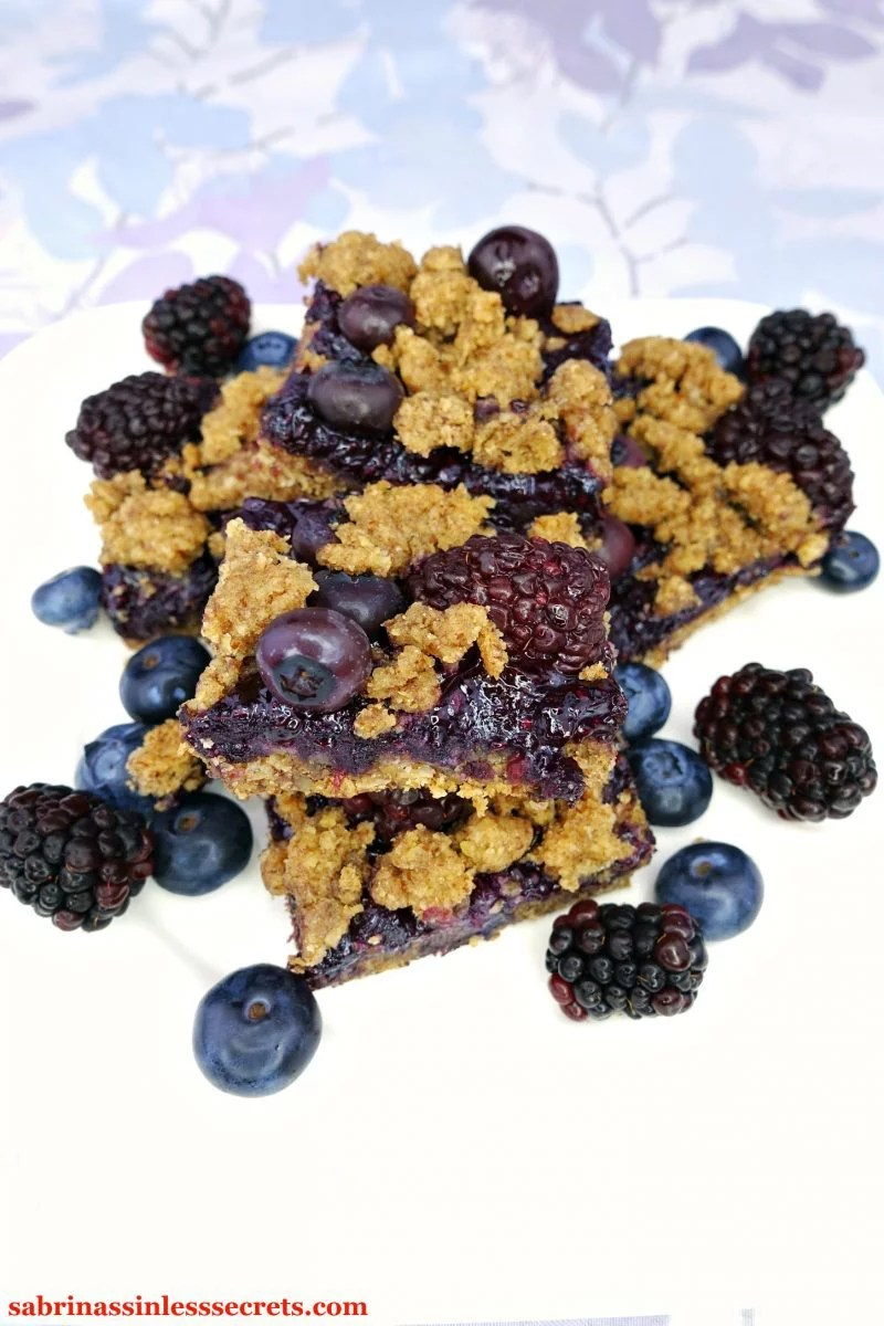 A stack of Black & Blueberry Gluten-Free Crumble Bars on a white plate with more bars, fresh blueberries and blackberries around them