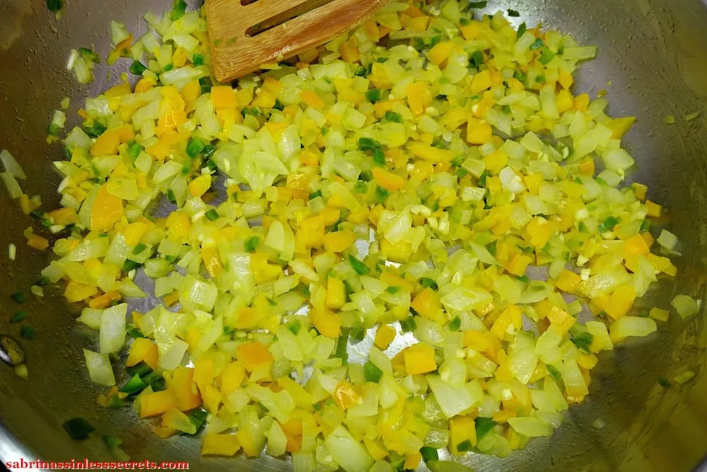 Cooked white onion, yellow bell pepper, jalepeno, and garlic in a stainless steel skillet