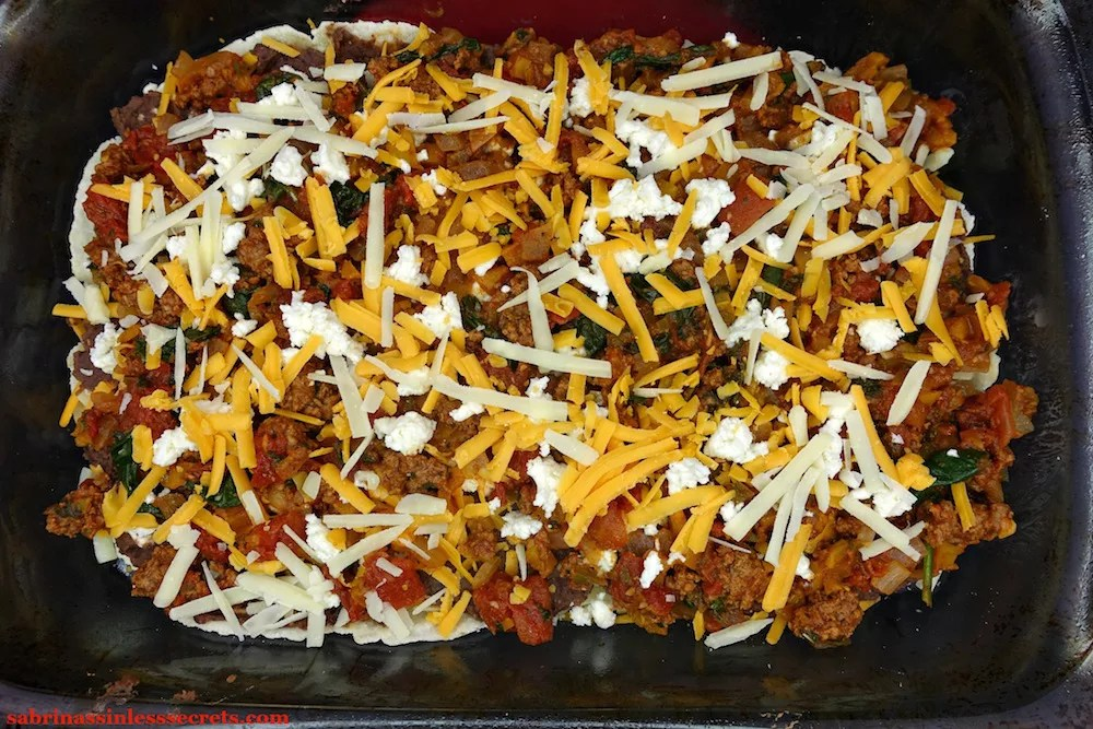 "Shredded cheddar, Parmesan, and mozzarella cheese over A beef and vegetable mixture over ""refried"" black beans, cheddar, Parmesan, and mozzarella cheese, and Easy Paleo Tortillas in a glass 9x13-inch pyrex baking dish"