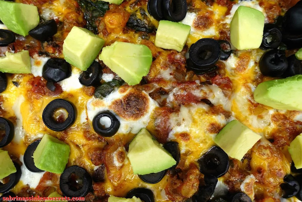 A homemade Gluten-Free Healthy Mexican Casserole, topped with sliced black olives and diced avocado