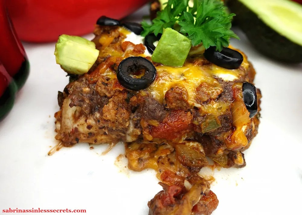 A serving square of Gluten-Free Healthy Mexican Casserole, garnished with parsley, sliced black olives, and dice avocado, on a white marble slab