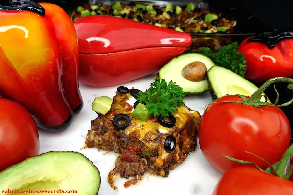 A serving of Gluten-Free Healthy Mexican Casserole, garnished with fresh parsley and diced avocado on a white marble slab with cut open avocados, whole red tomatoes on the vine, a glass, orange and red bell pepper, and a glass red chili pepper bowl, in addition to a casserole dish in the background