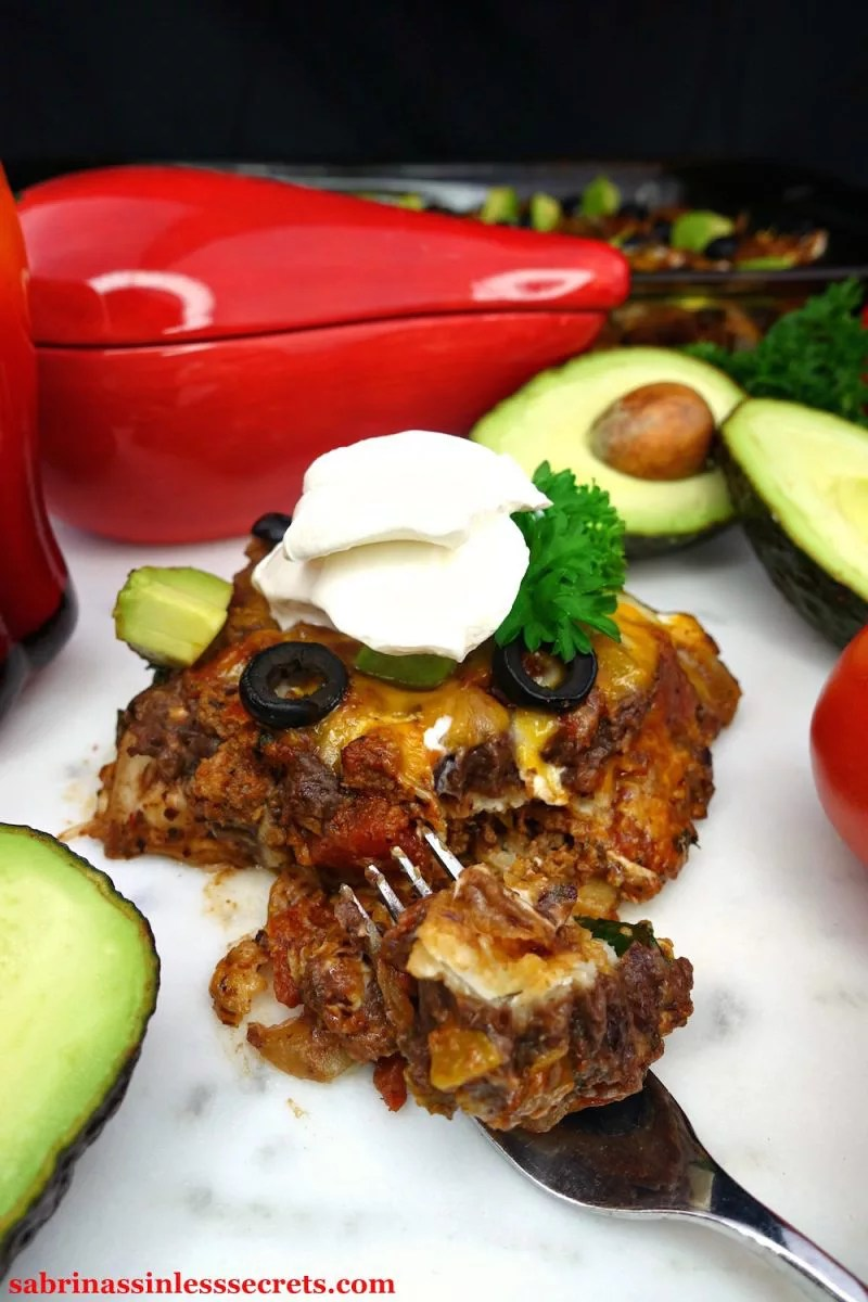 A serving square of a homemade Gluten-Free Healthy Mexican Casserole, garnished with black olive slices, diced avocado, parsley, and sour cream with a fork full of it in from of the casserole and cut open avocados, tomatoes on the vine, and a glass red chili pepper bowl in the background