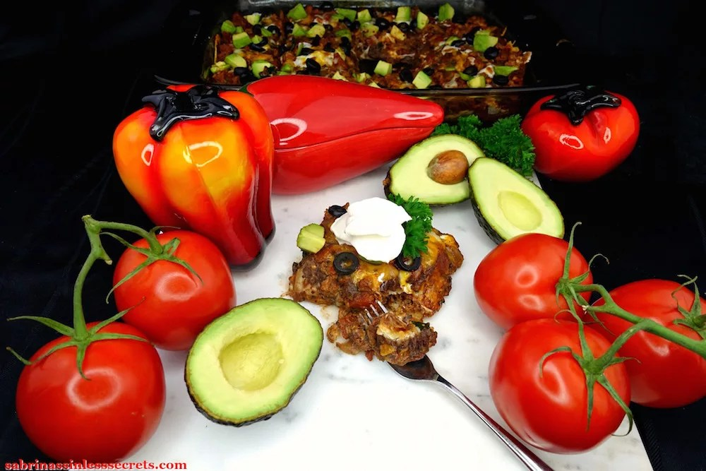 A serving of Gluten-Free Healthy Mexican Casserole, garnished with fresh parsley, diced avocado, and a dollop of sour cream on a white marble slab with cut open avocados, whole red tomatoes on the vine, a glass, orange and red bell pepper, and a glass red chili pepper bowl, in addition to a casserole dish in the background