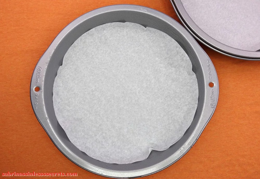 A 9-inch cake pan lined with round parchment paper on a orange background