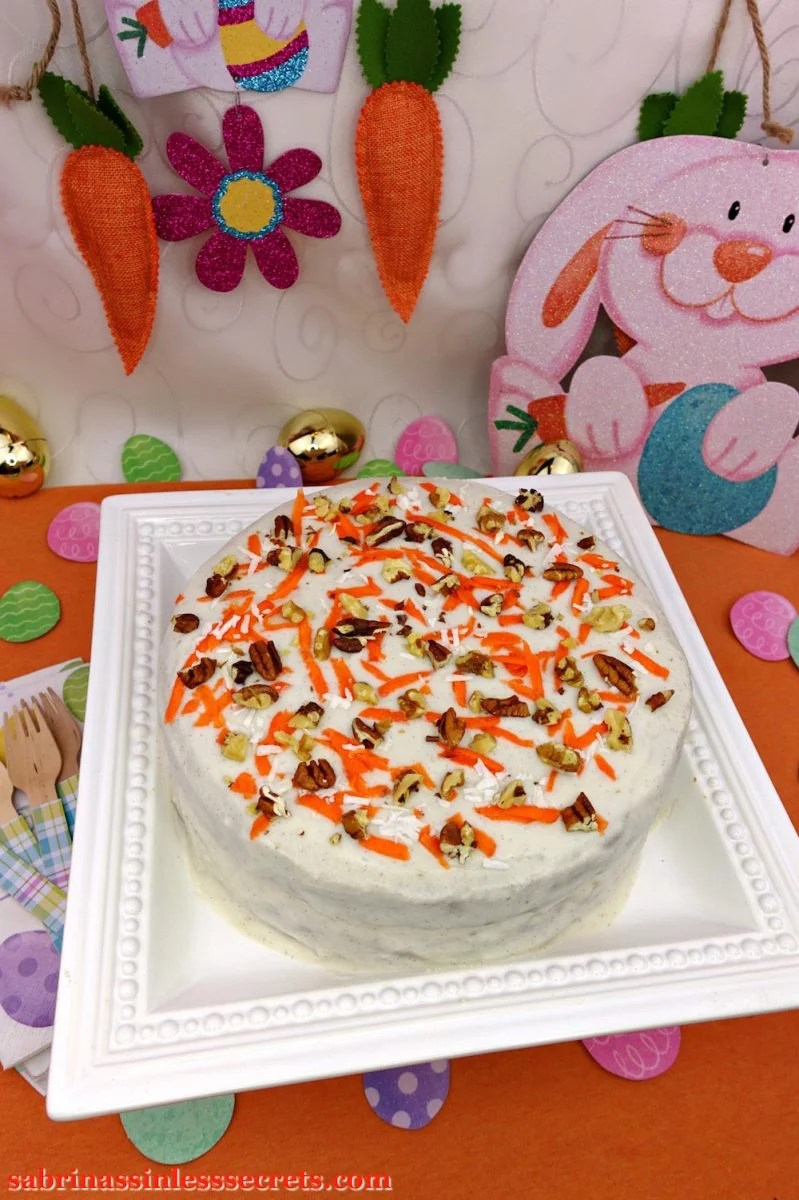 A Paleo Carrot Cake with Paleo Vanilla Bean Cream Frosting on a white square serving platter with Easter decorations in the background, such as Easter eggs, Easter Bunny, carrots, napkins, and wooden forks