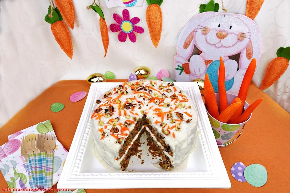 A homemade Paleo Carrot Cake with Paleo Vanilla Bean Cream Frosting with a piece cut out of it on a white square serving platter with Easter decorations of carrots, Easter eggs, and an Easter bunny in the background