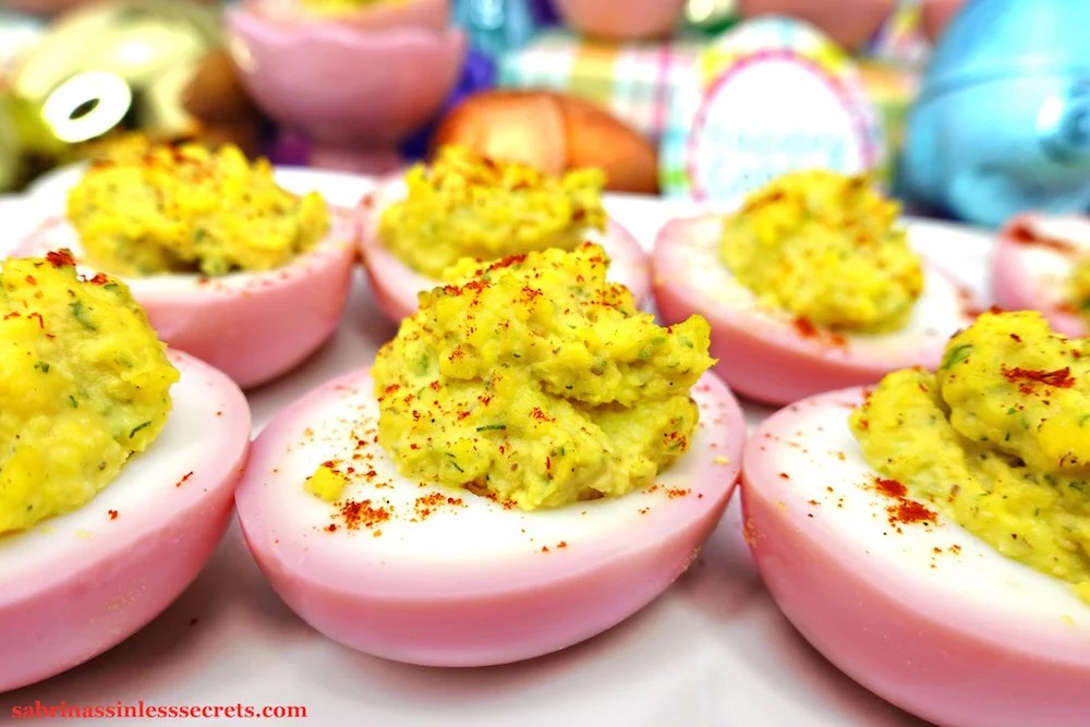 A close up of a Pink & Paleo Deviled Egg with more Pink & Paleo Deviled Eggs on a white tray