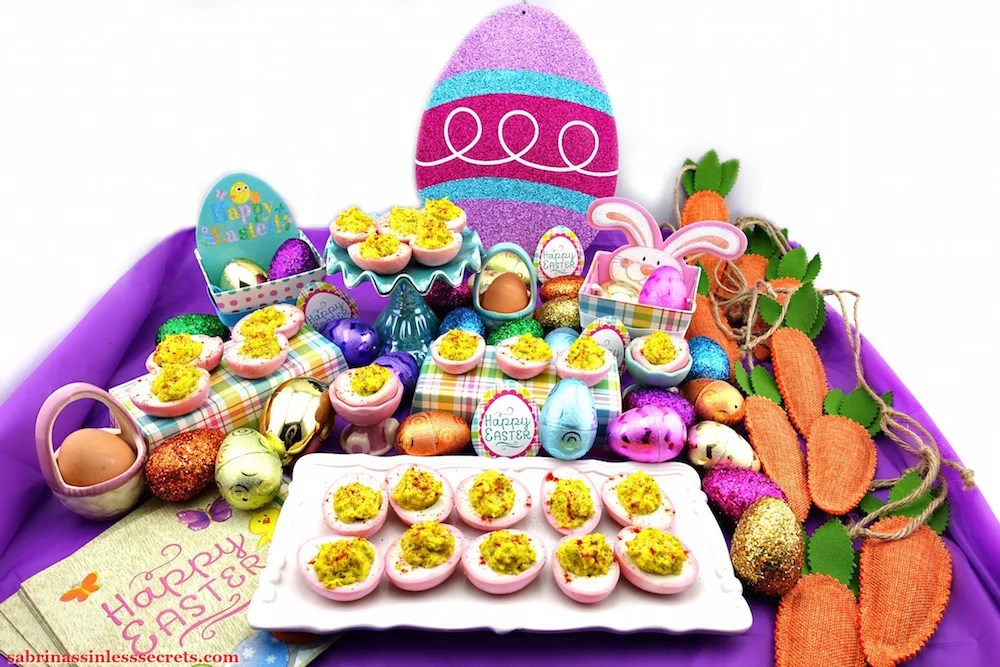 An arrangement of Pink & Paleo Deviled Eggs on serving dishes, surrounded by sparkly Easter eggs, carrots, and Easter napkins
