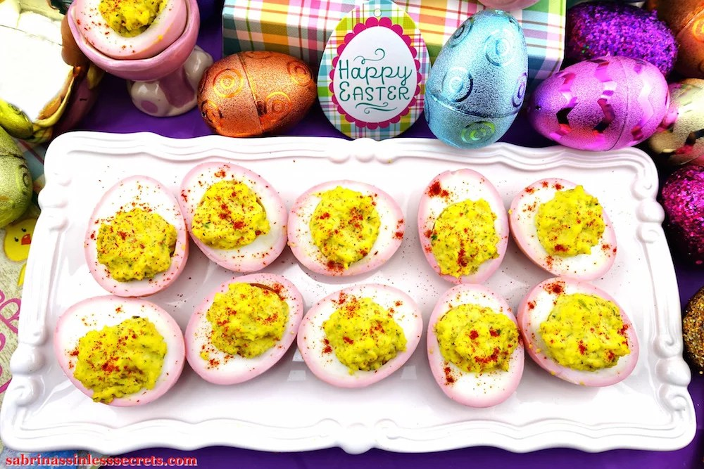 Ten Pink & Paleo Deviled Eggs on a white serving tray with sparkly Easter eggs, in the background