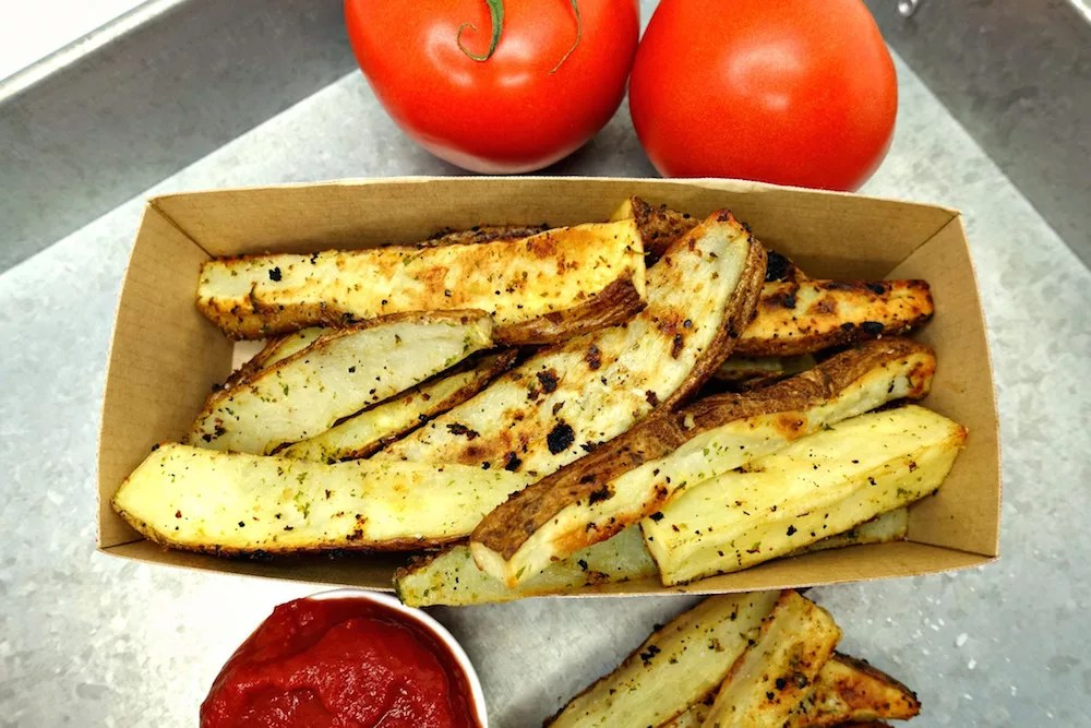 A basket full of Seasoned Oven Baked Crispy French Fries with two tomatoes on the vine next to it as well as a small white side cup of homemade Quick and Easy Paleo Ketchup and a pile of Seasoned Oven Baked Crispy French Fries