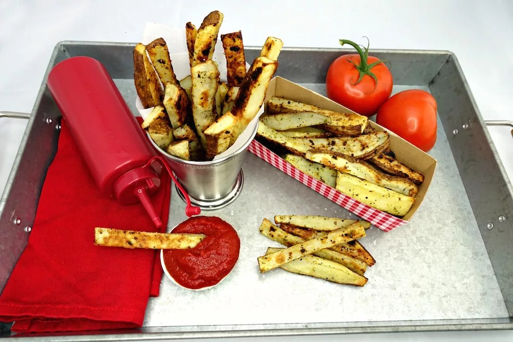 A stainless steel lap tray with Seasoned Oven Baked Crispy French Fries sprouting out of a stainless steel cup, laying in a white and red checkered basket, and on the tray with a fry dipped in a small white side cup of homemade Quick and Easy Paleo Ketchup and a red cloth napkin with a red plastic ketchup bottle atop it and two tomatoes off the vine in the background