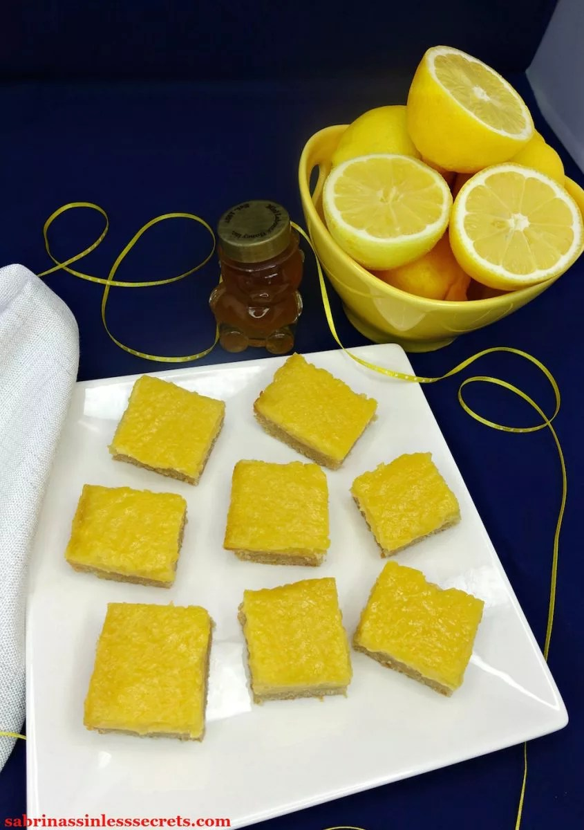 Homemade Paleo Lemon Bars with a Shortbread Crust on a white square plate over a midnight blue background with a sparkly white cloth napkin on the side, as well as a honey bear, a yellow bowl of whole and half-sliced lemons, and yellow with white dotted ribbon
