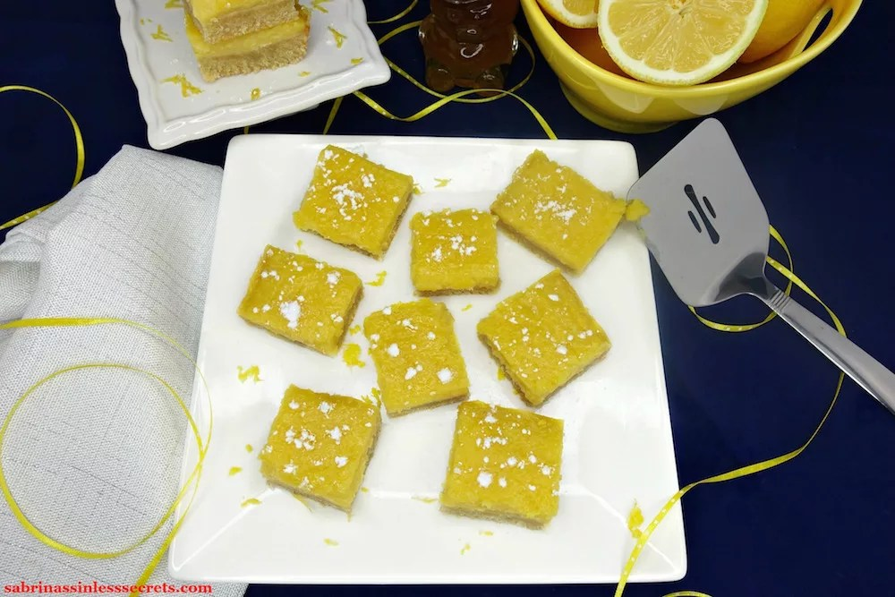 Homemade Paleo Lemon Bars with a Shortbread Crust sprinkled with tapioca starch and scattered throughout a white, square plate with a stainless steel square spatula on the side, in addition to yellow with white dotted ribbon, a white, sparkly cloth napkin, a honey bear, a stack of Paleo Lemon Bars with a Shortbread Crust on a white, small serving dish, and a yellow bowl of lemons on a midnight blue background