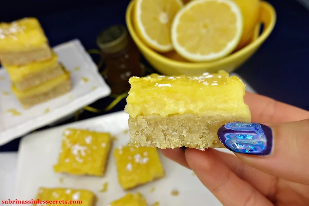A hand holding a homemade Paleo Lemon Bar with a Shortbread Crust and sprinkled with tapioca starch with more Paleo Lemon Bars with a Shortbread Crust in the background on a white plate and stacked on a small, white serving dish, in addition to a yellow bowl of half-cut lemons, a honey bear, and yellow with white dotted ribbon in the midnight blue background