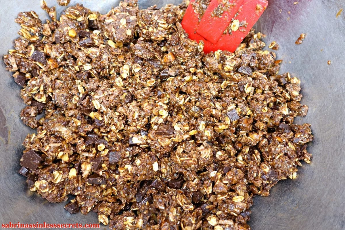 The mixture for Gluten-Free and Vegan No-Bake Chocolate Chunk Almond Coconut Energy Balls in a stainless steel bowl with a red spatula in it