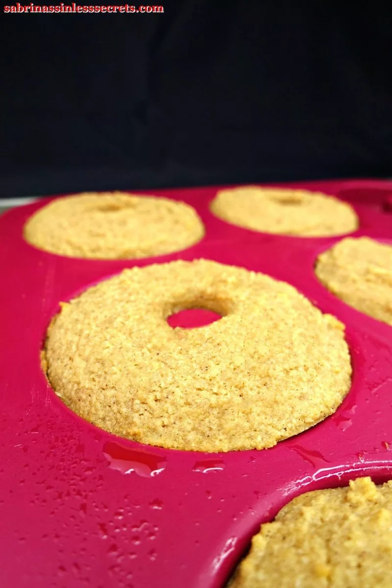 Paleo Maple Glazed Baked Donuts in a pink silicone donut pan fresh out of the oven